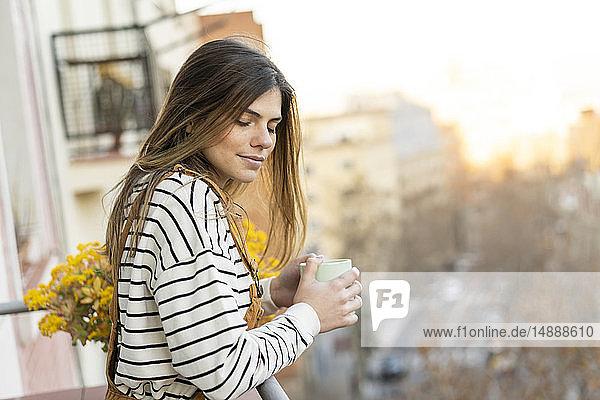 Porträt einer jungen Frau  die sich auf dem Balkon bei einer Tasse Kaffee entspannt