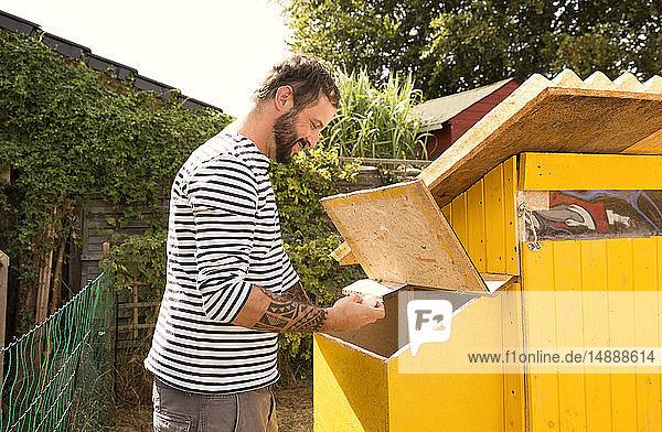 Mann sammelt Eier im Hühnerstall