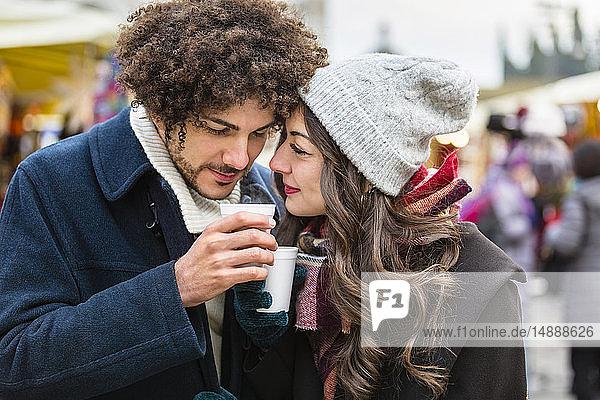 Glückliches  anhängliches junges Paar mit heißen Getränken auf dem Weihnachtsmarkt