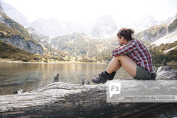 Austria  Tyrol  woman sitting on tree trunk at lake Seebensee