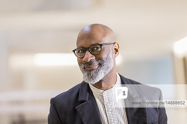 Portrait of bald mature businessman with grey beard wearing glasses