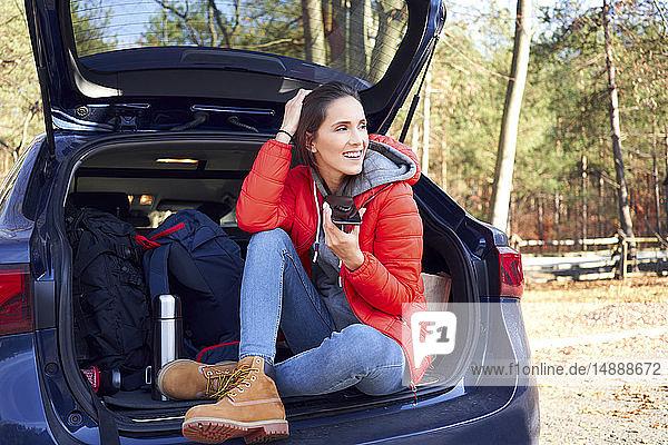 Glückliche Frau  die während einer Autofahrt ein Smartphone benutzt  während sie im Kofferraum sitzt