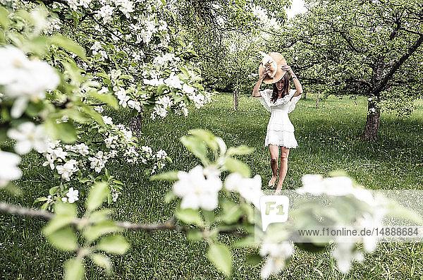 Junge Frau in weißem Kleid und Schlapphut geht barfuß im Garten mit blühenden Apfelbäumen