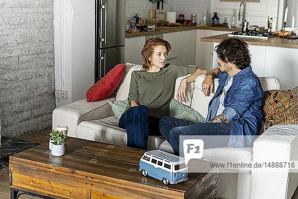 Ehepaar sitzt auf der Couch und plant eine Reise