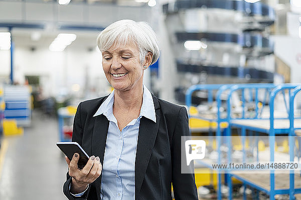 Smiling senior businesswoman looking at cell phone in a factory