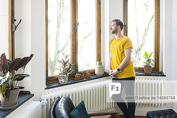 Pensive man in yellow shirt in stylish apartment looking out of window