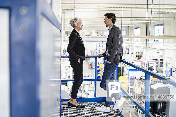 Lächelnder Geschäftsmann und leitende Geschäftsfrau im Gespräch in einer Fabrik