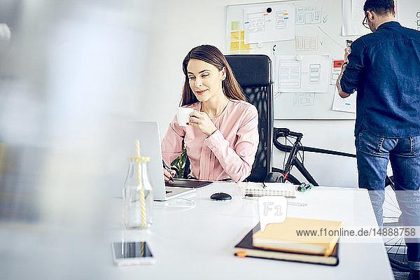 Frau arbeitet am Schreibtisch im Büro mit einem Kollegen im Hintergrund