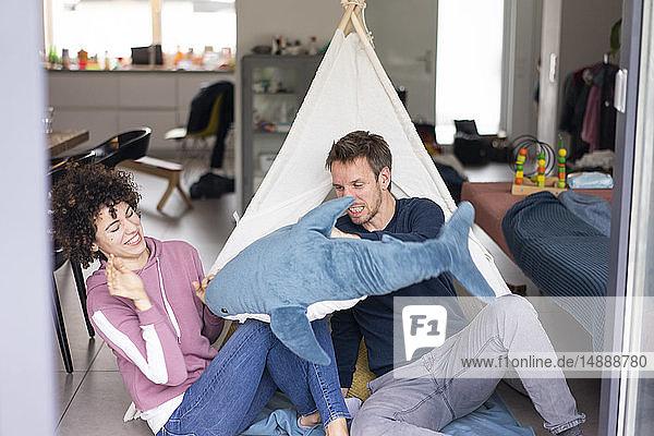 Pärchenkampf mit einer Spielzeugscharbe  die im Wohnzimmer vor einem Spielzelt sitzt