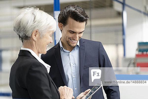 Lächelnder Geschäftsmann und leitende Geschäftsfrau mit Tablettengespräch in einer Fabrik