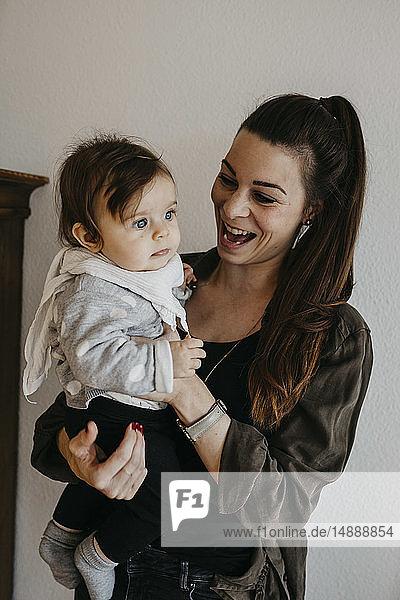 Glückliche Mutter trägt Mädchen zu Hause