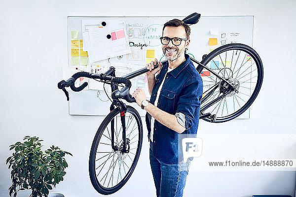 Porträt eines lächelnden Geschäftsmannes mit Fahrrad im Büro
