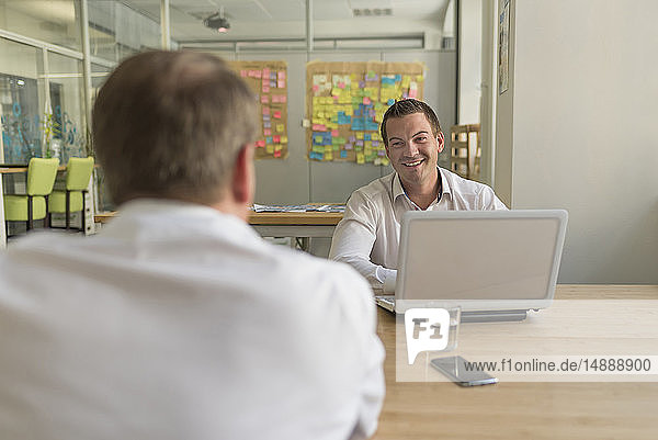 Two businessmen with laptop talking in office