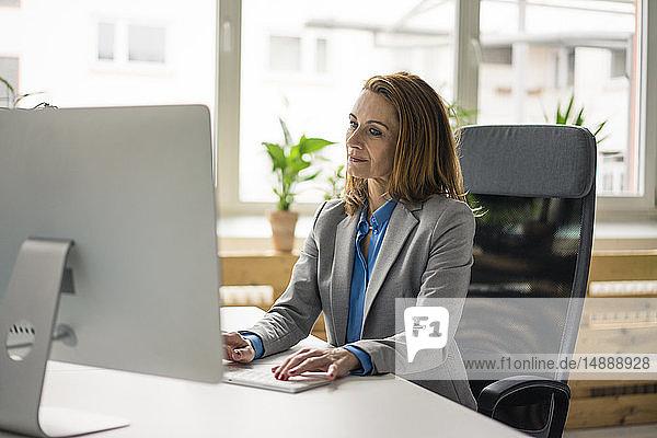 Geschäftsfrau  die im Büro sitzt und am PC arbeitet