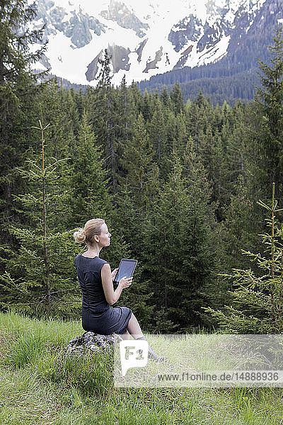 Italy  Alto Adige  Welschnofen  woman sitting in mountainscape using tablet