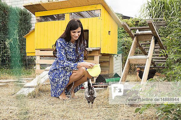 Lächelnde Frau beim Hühnerfüttern im Hühnerstall im Garten