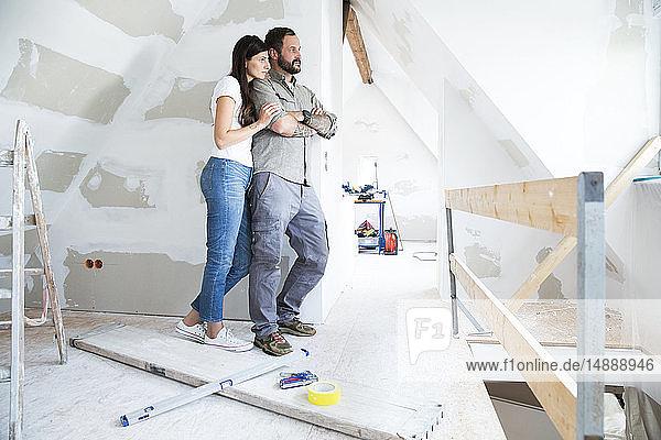 Ehepaar auf dem zu renovierenden Dachboden mit Blick aus dem Fenster