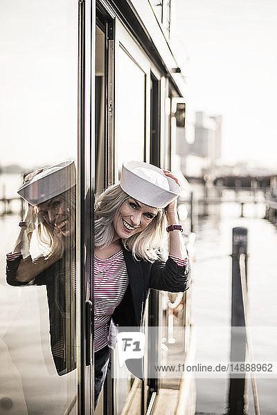 Geschäftsfrau mit Matrosenhut  die auf einem Hausboot arbeitet