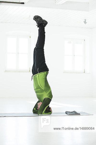 Mann macht sein Fitness-Regime  übt Kopfstand