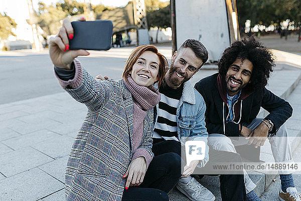Drei glückliche Freunde sitzen im Freien und machen ein Selfie