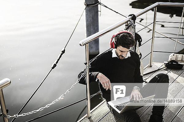 Geschäftsmann auf einem Hausboot mit Laptop  Kopfhörer tragend