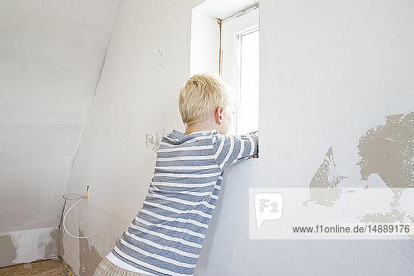 Junge schaut aus dem Fenster auf den zu renovierenden Dachboden