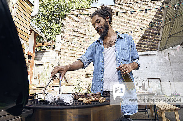 Young man preparing meat on a barbecue grill in a backyard