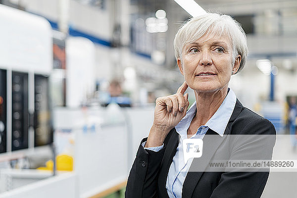 Portrait of senior businesswoman in a factory looking around