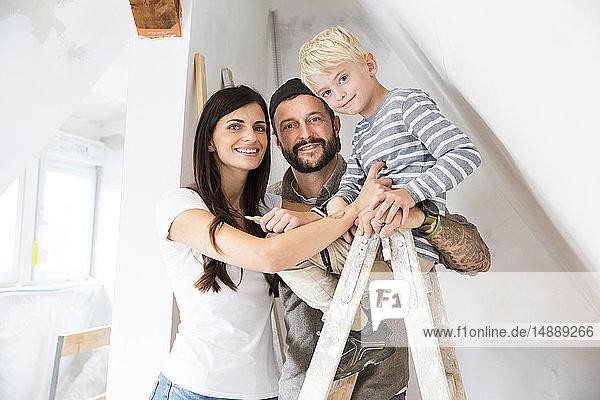 Porträt einer glücklichen Familie  die beim Dachbodenausbau arbeitet