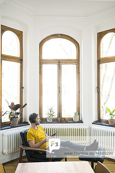 Casual man in yellow shirt with headphones sitting in Lounge Chair in stylish apartment