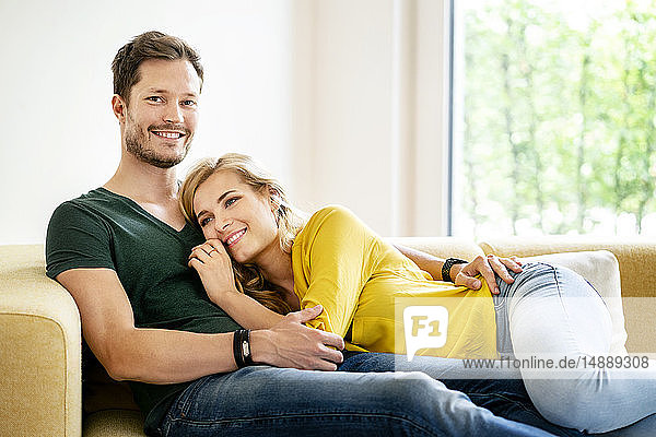 Couple sitting on couch in their new home  cuddling