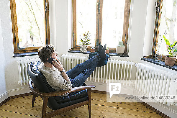 Casual man sitting in Lounge Chair in stylish apartment talking on the phone
