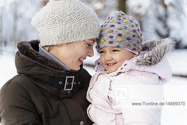 Glückliche  liebevolle Mutter trägt Tochter im Winter