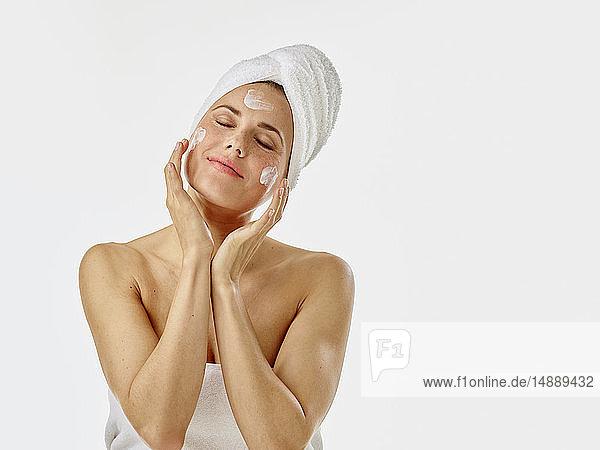 Junge Frau trägt Gesichtscreme auf ihr Gesicht auf