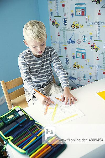 Junge malt auf Papier am Schreibtisch im Kinderzimmer