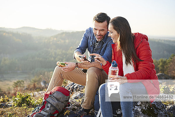 Happy couple on a hiking trip in the mountains taking a break looking at cell phone