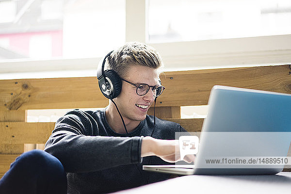 Smiling young man using laptop listening to music with headphones