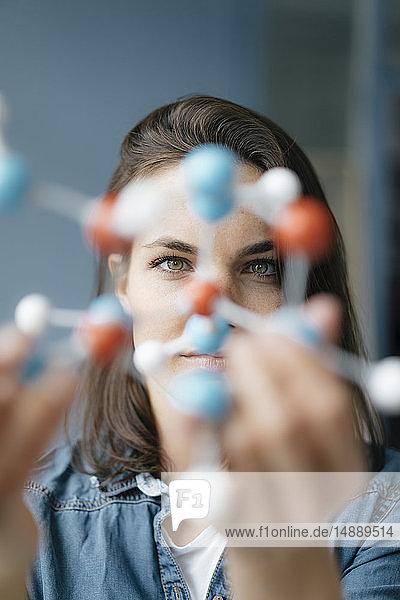 Weibliche Wissenschaftlerin untersucht Molekülmodell  sucht nach Lösungen