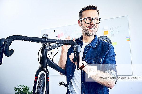 Lächelnder Geschäftsmann mit Fahrrad im Büro