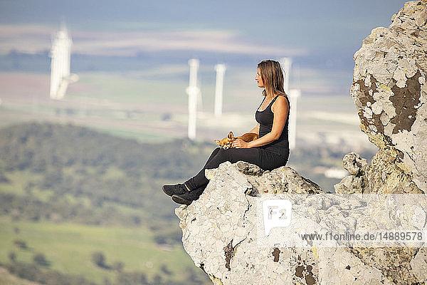 Junge Frau mit Schoßhund sitzt auf einem Felsen und schaut in die Ferne