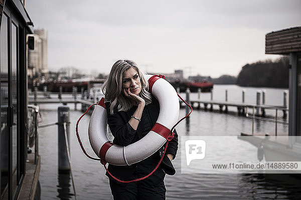 Geschäftsfrau steht auf einem Hausboot  sieht besorgt aus und hat einen Lebensretter dabei