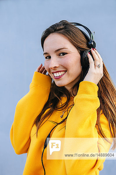 Portrait of smiling young woman listening to music with headphones