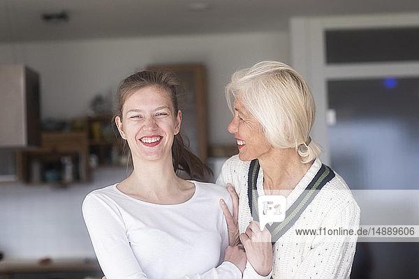 Porträt einer lachenden jungen Frau und ihrer Mutter zu Hause