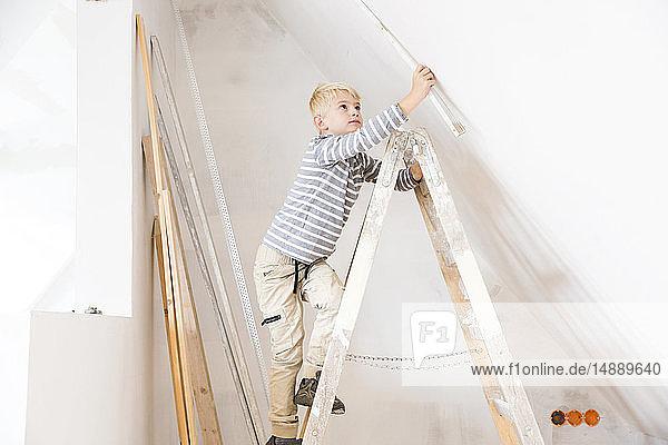 Junge mit Meterstab auf Leiter-Messwand im zu renovierenden Dachgeschoss