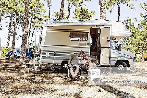 Frankreich  Gironde  glückliches Paar sitzt vor dem Wohnmobil auf dem Campingplatz