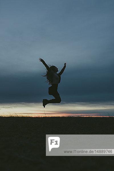 Silhouette einer glücklichen Frau in der Natur  die bei Sonnenuntergang in die Luft springt