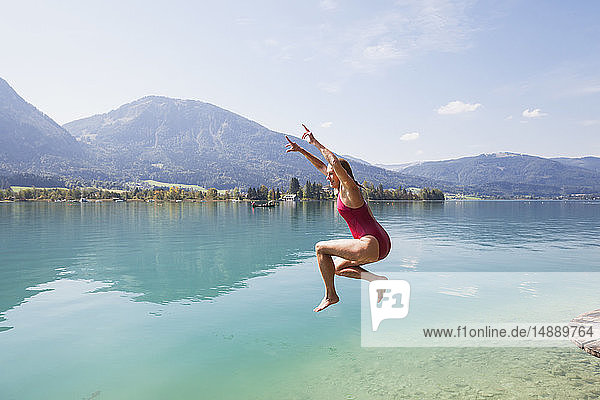 Austria  Alps  Salzburg  Salzkammergut  Salzburger Land  Wolfgangsee  woman jumping into lake