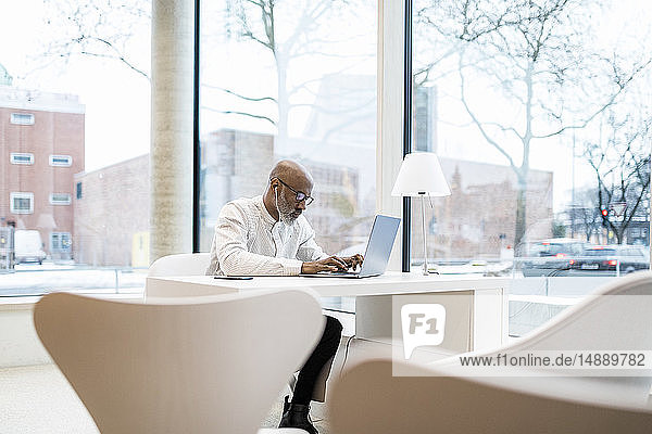 Mature businessman with earphones sitting at desk working on laptop