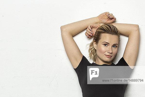 Porträt einer blonden Frau in schwarzem Trikot vor weißem Hintergrund