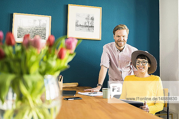 Portrait of happy couple at wooden table in their home office holding tablet